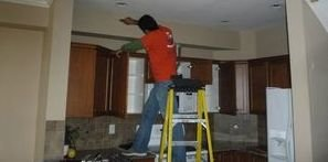 Water Damage Restoration Tech Cleaning Mold Off Ceiling