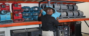 Water Damage Restoration Technician Mobilizing Air Movers